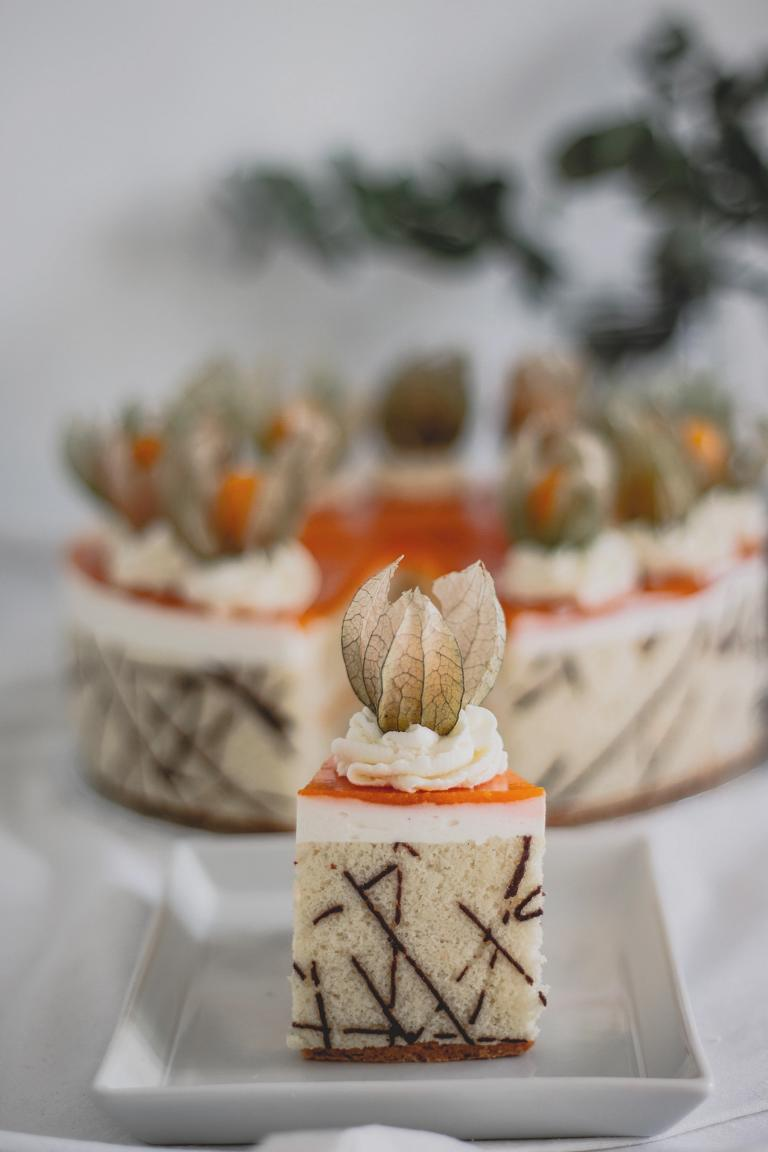 Ein Tortenstück, im Hintergrund die Torte
