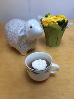 chocolate custard in a teacup with whipped cream and next to a ceramic sheep and flowers