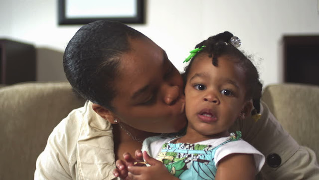 African woman kissing her daughter