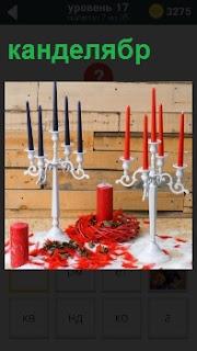 На столе стоят разные канделябры и свечи красного и черного цветов