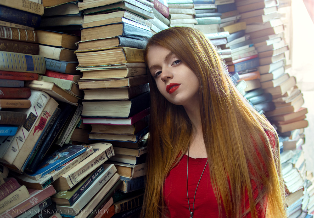 Portrait of woman with red hair and lips in red dress among the books