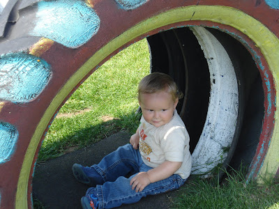 Baby Boy sitting in a hollow Tractor tyre