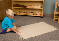 NAMC montessori preschool first day boy rolling out mat