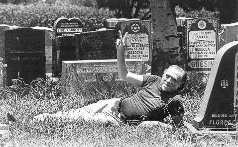 Fotografía de Charles Bukowski posando en un cementerio