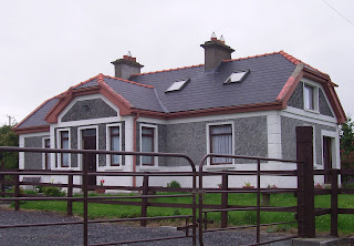 Irish cottage, rebuilt into a two story house, mixed architectural style, stone walls, fence, house with driveway