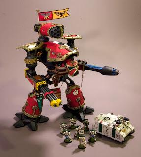 Un titán Reaver, modelo muy muy antiguo, al lado de un rhino y marines espaciales modernos.
