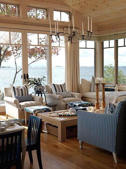 Blue and white great room overlooking water with windows