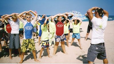 Camp counselor Eric Colbert helps Aloha kids start the day off right with stretching and exercise at Aloha Beach Camp.