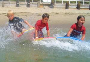 Three happy campers boogie boarding at Aloha Beach Camp
