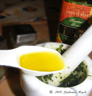 Photo of adding Trader Joe's Olive Oil to Pesto Recipe