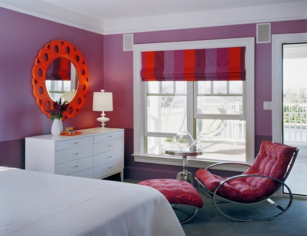 Purple bedroom by Ghislaine Vinas with white dresser, orange mirror, chaise lounge and purple and orange striped Roman shades