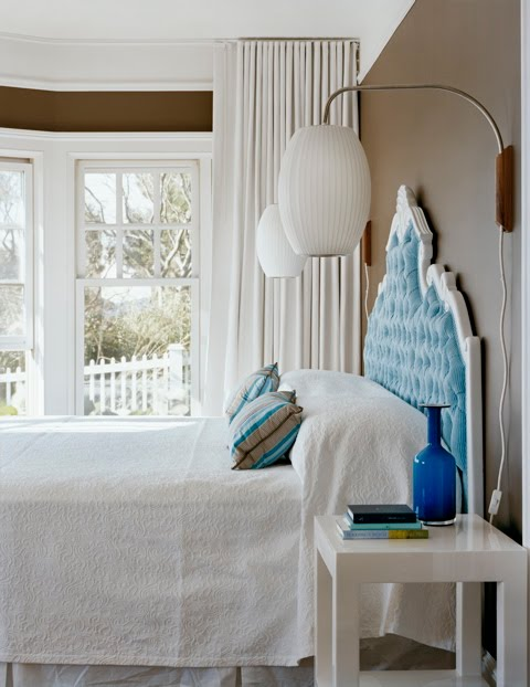 Turquoise and brown master bedroom by Ghislaine Vinas with a light blue tufted headboard with white trim and a modern white side table