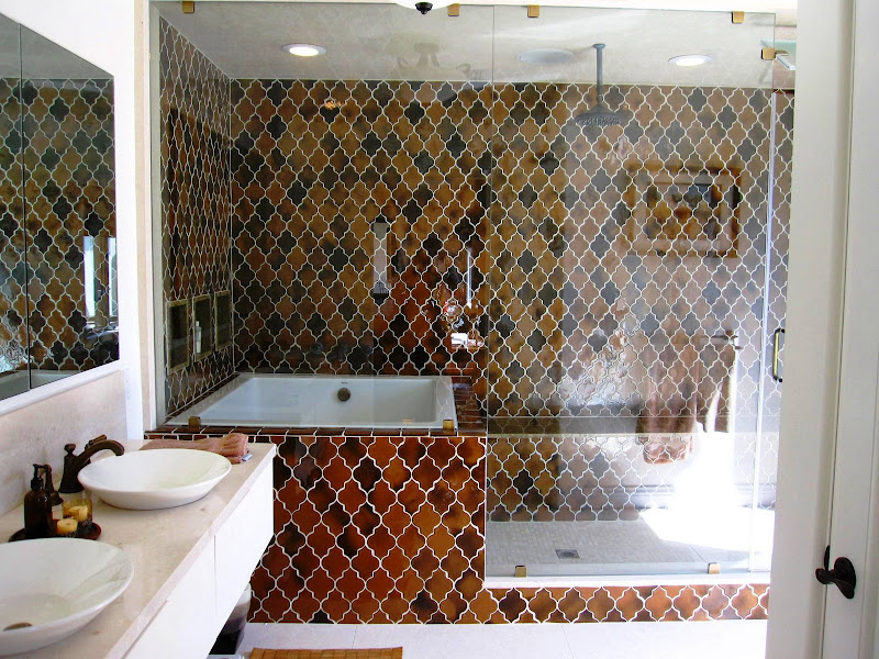 Bathroom in a Los Angeles home with a glass enclosed combination tub and shower with bronze glazed tiles