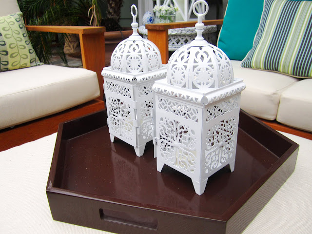 Two white metal Moroccan style lanterns on brown tray