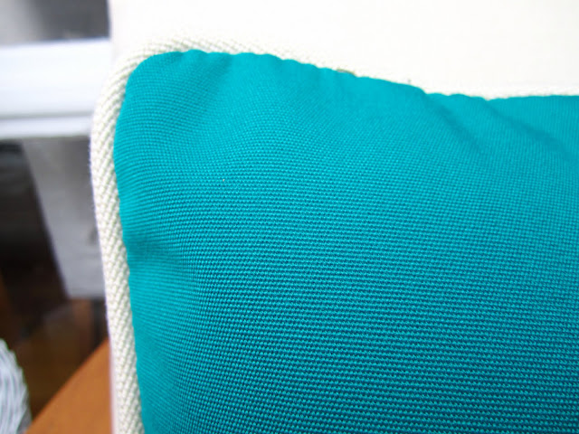 Close up of turquoise pillow with white trim