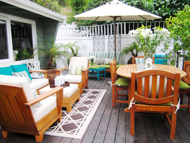 Outdoor deck with refurbished and painted furniture and brightly colored accessories