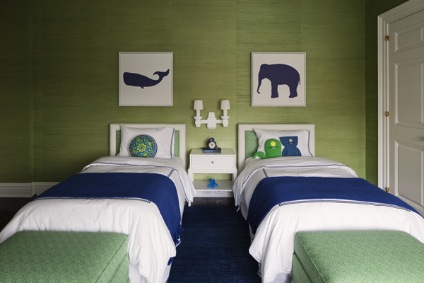 Bedroom with green walls, two twin beds with white and green headboards, white bedding with blue trim, a blue throw and green ottomans at the foot of the bed