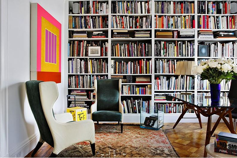 Library with floor to ceiling bookshelf full of books, parquet wood tiling, two wing back armchairs, a Moroccan rug, and a coffee table with wood legs and a glass top
