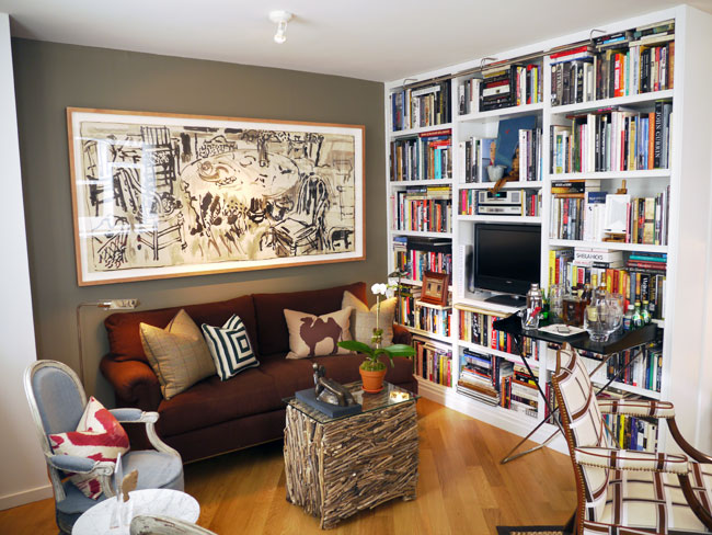 Living room with floor to ceiling built in bookshelf stuffed with books and a tv, a brown sofa, a coffee table made out of twigs with a glass top, wood floor, grey walls, and a powder blue Louis XIV chair with a red and white accent pillow