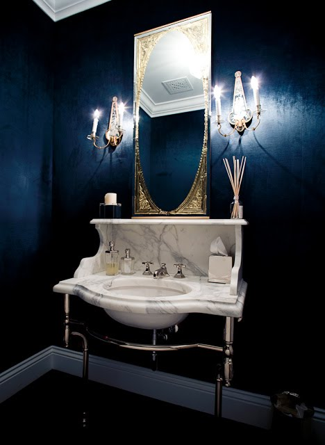 Bathroom with navy blue walls, a large art deco gilded mirror, two wall mounted candlesticks, dark wood floor, moulded ceiling and a marble console sink