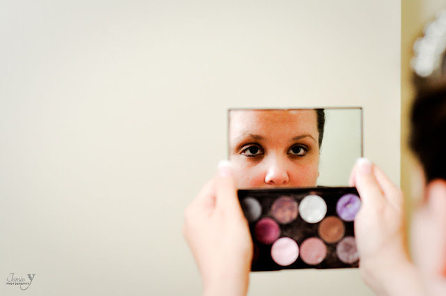 Getting ready photography of bride looking in compact mirror for her las vegas wedding