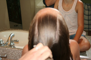 """Top view of young girl's hair being styled into """"Knots into Side Ponytail"""" hairstyle"""