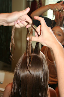 "Girl's hair being styled into ""Double Knot Ponytail"""