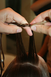 """Close up view of young girl's hair being styled into """"Knots into Side Ponytail"""" hairstyle"""