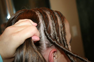 "Side view of Young girl's hair being styled into ""Triple Twists and Messy Buns"""