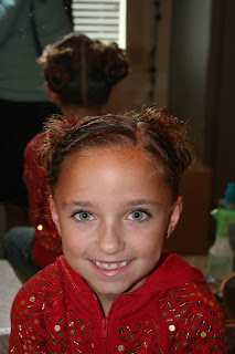"Portrait view of young girl's hair styled into ""Triple Twists and Messy Buns"""