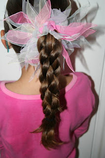 "Back view of young girl modeling ""Triple-Twist Ponytail' hairstyle"