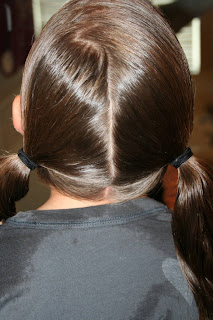 """Back view of young girl's hair being styled into """"Basic Twisty Buns"""" hairstyle"""