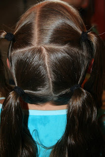 """Back view of young girl's hair being styled into """"4 Messy-Pigtail Twists"""" hairstyle"""
