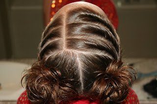 """Top view of young girl's hair being styled into """"Curls After Triple Twists w/ Messy Buns"""" hairstyle"""