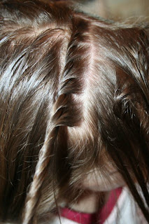 "Close up of young girl's hair being styled into ""Hair Twists into Messy Buns"" hairstyle"