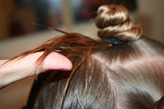 "Close up view of young girl's hair being styled into ""Holiday Twisty Buns"" hairstyle"