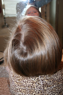 back view of young girl's hair being styled into 3-barrel curl hairstyle on her a-line bob