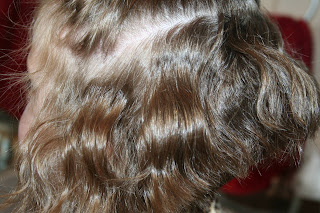 side view of young girl's hair being styled into 3-barrel curl hairstyle on her a-line bob