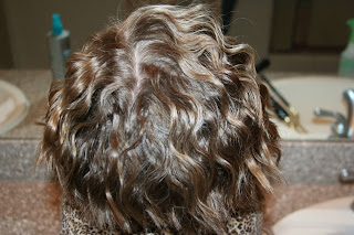 back view of young girl modeling 3-barrel curl hairstyle on her a-line bob