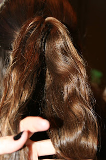 "Back view of young girl's hair being styled into ""Flip Braided Heart"" hairstyle"