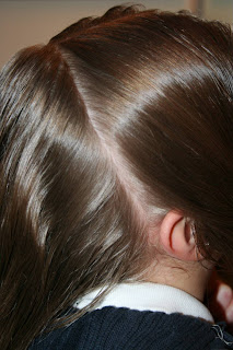 "Side view of a young girl's hair being styled into ""French Designer Heart"" hairstyle"