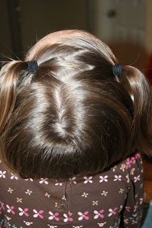 "Top view of a young girl's hair being styled into ""Heart Pigtail"" hairstyle"