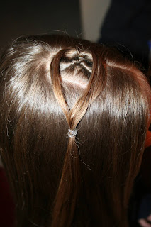 "Side view of young girl having her hair styled as ""teen heart"" hairstyle 1"