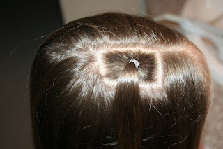 "Top view of young girl having her hair styled as ""teen heart"" hairstyle 1"