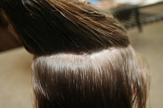 """Back view of young girl's hair being styled into """"The Bun-Hawk"""" hairstyle"""