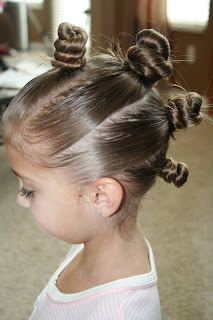 """Side view of young girl modeling """"The Bun-Hawk"""" hairstyle"""