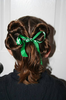 "Back view of young girl modeling ""Two-Leaf Clover"" hairstyle styled with green ribbon hair accesory"