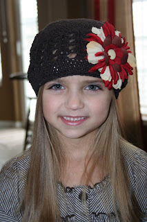Portrait view of young girl modeling chocolate-brown beanie with a red and cream big flower