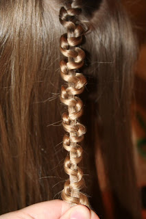 "Close up view of young girl's hair being styled into ""Teen Slide-Up Braid"" hairstyle outside"