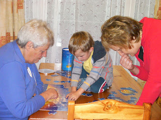 boy playing board games with mother and grandmother on pine table